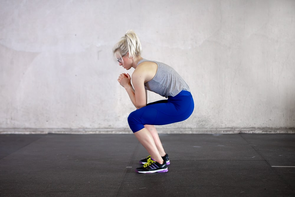 woman hunching back during a squat