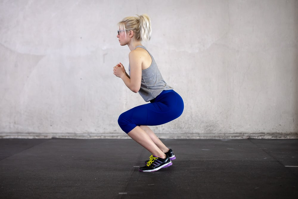 woman lifting heels of the floor while doing a squat